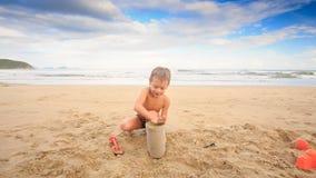 Os jogos pequenos do menino com areia molhada enchem a cubeta na praia do mar vídeos de arquivo