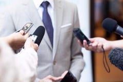 Os journalistas que fazem meios entrevistam com a pessoa irreconhecível ou o político do negócio fotos de stock royalty free