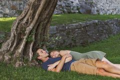 Os jovens acoplam-se no amor que senta-se sob uma ?rvore em um castelo fotos de stock royalty free