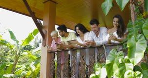 Os jovens agrupam usando dispositivos no terraço do verão na floresta tropical, amigos da raça da mistura que surfam meios sociai filme