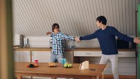 Os jovens alegres de amor do marido e da esposa são de dança e de beijo na cozinha em casa que escutam a música e que apreciam vídeos de arquivo