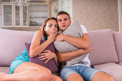 Os jovens amedrontados acoplam o filme assustador de observação na tevê foto de stock royalty free