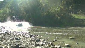 Os jovens apreciam montar uma bicicleta do quadrilátero ao longo de um rio raso filme