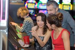 Os jovens bonitos aproximam o slot machine no casino fotografia de stock royalty free