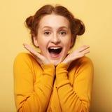 Os jovens bonitos surpreenderam a mulher do redhair sobre o fundo amarelo fotografia de stock