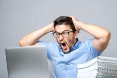 Os jovens chocaram o homem na camisa azul usando o portátil Fotos de Stock