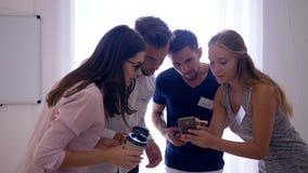 Os jovens com crachás guardam bolos e café durante a ruptura, os trabalhadores de escritório comunicam-se e olham-se na tela do t vídeos de arquivo