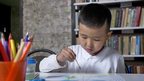 Os jovens concentraram a pintura asiática da criança no papel e o assento atrás da tabela, menino que faz trabalhos de casa, fund filme
