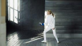 Os jovens concentraram a prática da mulher do esgrimista que cerca exercícios e que treina para a competição dos Jogos Olímpicos  Imagens de Stock