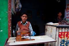 Os jovens costuram o trabalho em uma máquina de costura Fotos de Stock