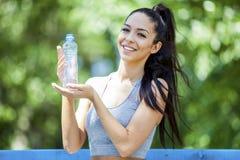Os jovens couberam a menina bonita que promove a água potável após o exercício exterior foto de stock