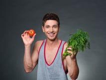 Os jovens couberam o instrutor e o nutricionista que guardam uma bacia de vegetais Foto de Stock