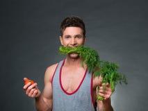 Os jovens couberam o instrutor e o nutricionista que guardam uma bacia de vegetais Imagem de Stock