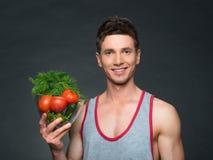 Os jovens couberam o instrutor e o nutricionista que guardam uma bacia de vegetais Imagem de Stock Royalty Free