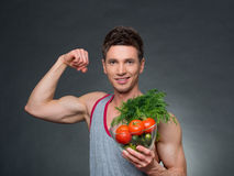 Os jovens couberam o instrutor e o nutricionista que guardam uma bacia de vegetais Foto de Stock Royalty Free
