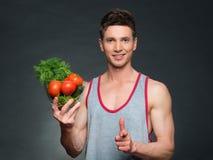 Os jovens couberam o instrutor e o nutricionista que guardam uma bacia de vegetais Fotografia de Stock