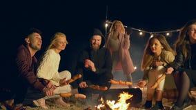 Os jovens cozinham salsichas no fogo e na dança quando aprecie o feriado fora video estoque