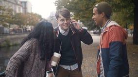 Os jovens de nacionalidades diferentes têm o divertimento e relaxam n o ar fresco vídeos de arquivo