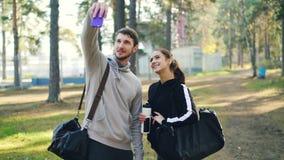 Os jovens desportivos dos amigos felizes estão tomando o selfie usando o smartphone após a prática exterior no parque O homem e a video estoque