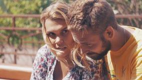 Os jovens em pares do amor usam o smartphone que senta-se no banco Dia ventoso do verão chatting vídeos de arquivo