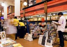Os jovens escolhem os compartimentos e os livros dentro da livraria popular Foto de Stock