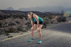 Os jovens esgotaram a mulher do esporte que corre fora na estrada asfaltada que respira Imagem de Stock Royalty Free