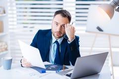 Os jovens esgotaram o gerente que senta-se com sua cabeça que inclina-se em seu punho Imagem de Stock