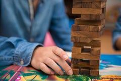 Os jovens estão jogando o jogo da madeira do jenga Imagem de Stock