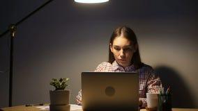 Os jovens focalizaram a mulher que usa o portátil que trabalha horas extras atrasadas no PC video estoque
