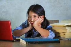 Os jovens forçaram e frustraram a menina coreana asiática do estudante que trabalha duramente com a pilha do laptop e dos livros  fotos de stock