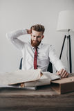 Os jovens forçaram o homem de negócios com os originais e os dobradores que sentam-se na tabela Fotografia de Stock Royalty Free
