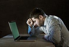 Os jovens forçaram o homem de negócios que trabalha na mesa com o portátil do computador na frustração e na depressão Imagens de Stock Royalty Free