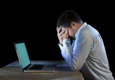 Os jovens forçaram o homem de negócios que trabalha na mesa com o portátil do computador na frustração e na depressão Fotografia de Stock