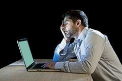 Os jovens forçaram o homem de negócios que trabalha na mesa com o portátil do computador na frustração e na depressão Foto de Stock