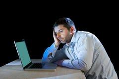 Os jovens forçaram o homem de negócios que trabalha na mesa com o portátil do computador na frustração e na depressão imagens de stock
