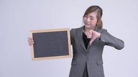 Os jovens forçaram o quadro-negro asiático da terra arrendada da mulher de negócios e da doação os polegares para baixo filme