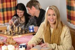Os jovens gastam a casa de campo do país do feriado de inverno Fotografia de Stock