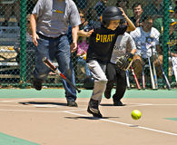 Os jovens golpeiam o corredor à primeira base Foto de Stock Royalty Free