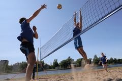 Os jovens jogam o voleibol de praia amador imagem de stock royalty free