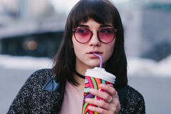 Os jovens na menina vestida à moda da mola em vidros cor-de-rosa que anda em torno da cidade e do café bebendo coloriram o copo imagens de stock