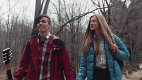 Os jovens no amor que andam abaixo do outono abandonaram o parque Um menino está guardando uma guitarra, menina com um cabelo lon vídeos de arquivo