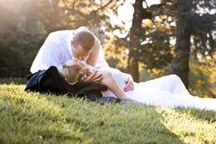 Os jovens no amor wed recentemente os pares que relaxam no campo na luz solar dourada da tarde Imagens de Stock