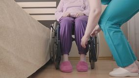 Os jovens nutrem o inquietação de uma mulher deficiente mais idosa na cadeira de rodas e transferem-na na cama