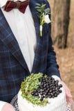 Os jovens preparam guardar um bolo de casamento rústico com mirtilo e hortaliças, primavera foto de stock
