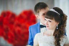 Os jovens preparam o beijo da noiva em um interior do estúdio fotografia de stock royalty free
