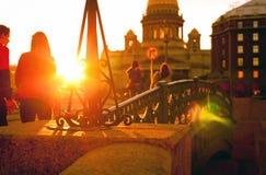 Os jovens que andam no por do sol ao longo do passeio perto do St Imagem de Stock Royalty Free