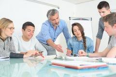 Os jovens que o professor discute comunicam a sala de aula da universidade fotos de stock royalty free