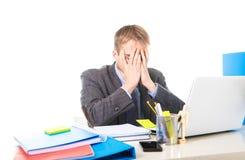 Os jovens sobrecarregaram e oprimiram o homem de negócios que cobre seus esforço e dor de cabeça do sofrimento da cara Fotografia de Stock Royalty Free