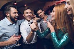 Os jovens têm o divertimento em um clube noturno Três homens e três mulheres encenaram uma batalha musical Fotos de Stock