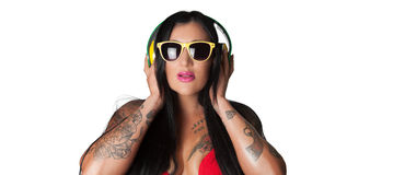 Os jovens tattooed pesadamente a mulher que escuta a cabeça do estilo do DJ Fotos de Stock